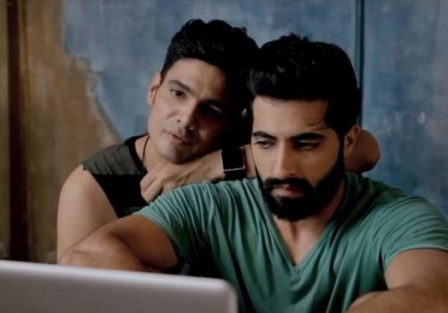 """Screengrab from """"Baby Steps"""", a gay couple sit together in front of a laptop in an intimate pose"""