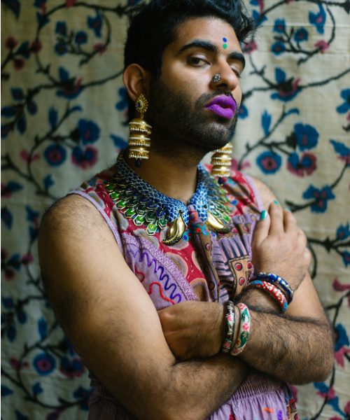 Gender non-conforming poet Alok Vaid Menon. They are dressed in a vibrant sleeveless dress, jewellery and makeup.