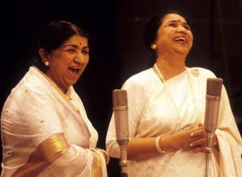 Picture of singers Lata Mangeshkar and Asha Bhonsale,. They are both dressed in sarees.
