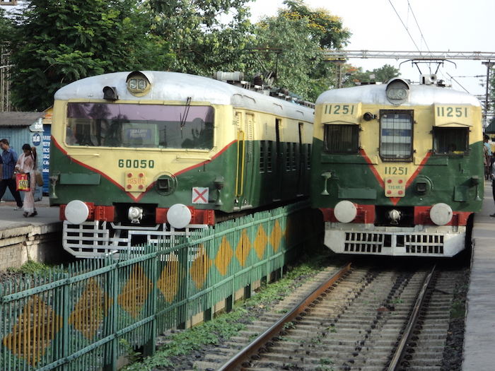 Picture of two trains, one already present on the platform, and another approaching the platform. They are both green in colour with off-white stripes on them