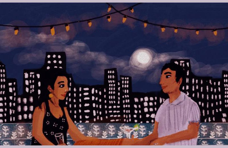A young woman and young man are smiling at each other across a table overlooking a city skyline. The moon is full and there are fairy lights strung above them. There is a white trellis behind the woman. Credit: Upasana Agarwal.