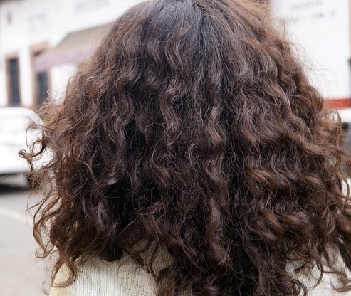 A woman with curly hair faced away from the camera
