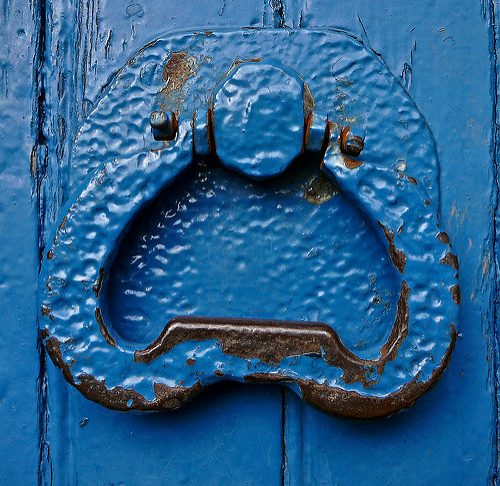 Picture of a wooden door and door knocker, painted bright blue