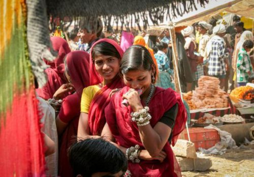 Picture of a group of young women from rural UP. They are in a market, laughing together.