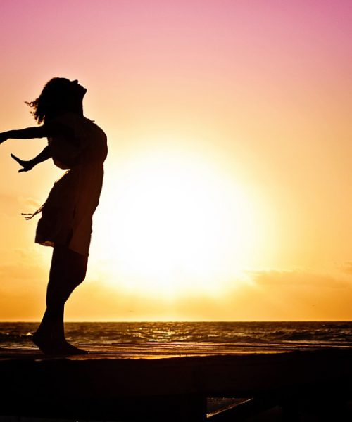 a single woman's silhuoette with her arms outstretched and the sunlight illuminating her body