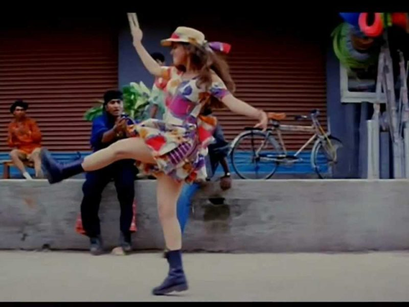 A still from the film Rangeela a girl in a white dress with floral patterns and a hat dances with one leg up