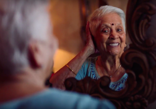 a woman with grey hair looks into the mirror and smiles