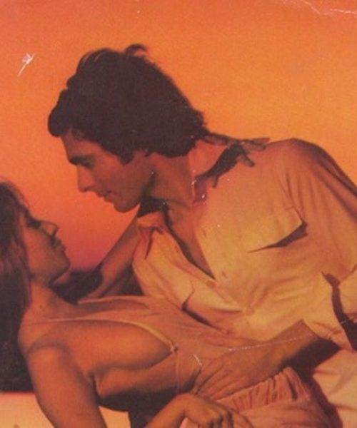 against an orange backdrop, a man leaning down to face a woman, they are in an intimate pose