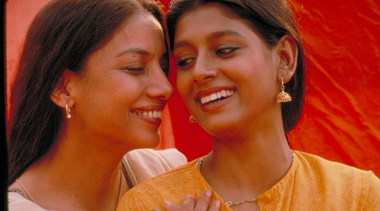 "Still from ""Fire"", showing two women standing together intimately, smiles on their faces"