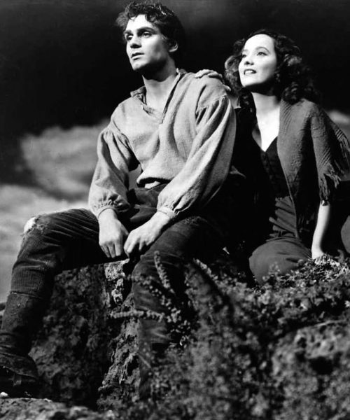 black and white image of a man and woman sitting on a hill looking out at nature