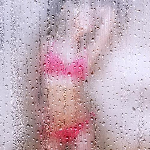 porn: a blurred image of a women clad in pink lingerie seen behind a fogged glass
