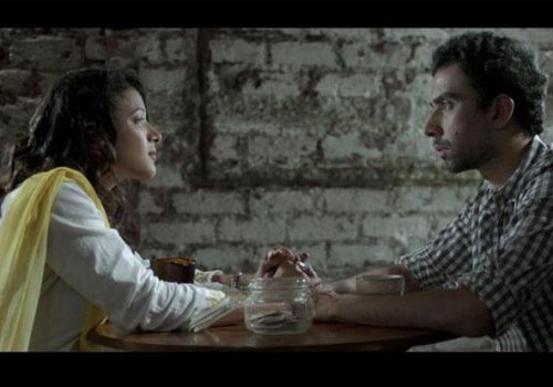 Still from 'Interior Cafe Night': a couple sits facing each other
