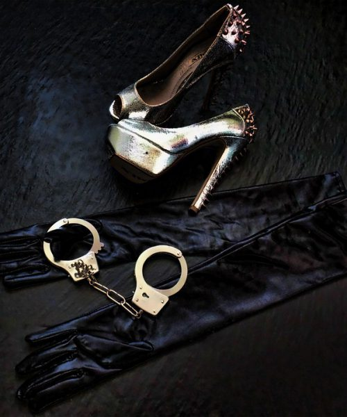 Silk black gloves, along with a pair of heels and handcuffs