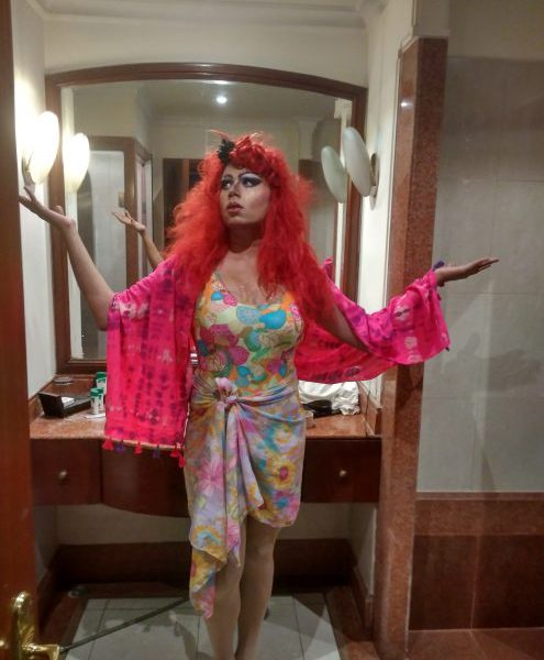 A drag queen dressed in a long dress and with a red wig and makeup