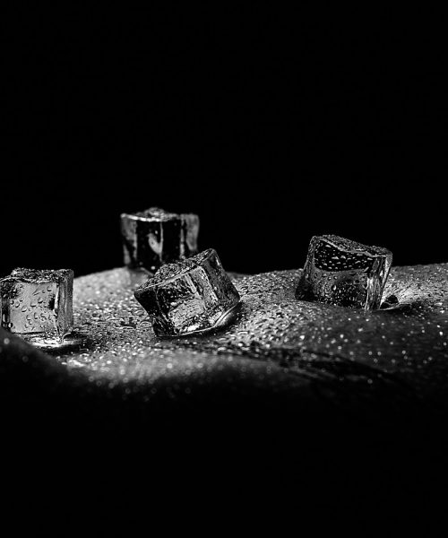 Black and white image of ice cubes on exposed skin