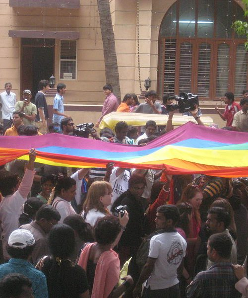 an image of a rainbow pride flag being carried by a large crowd
