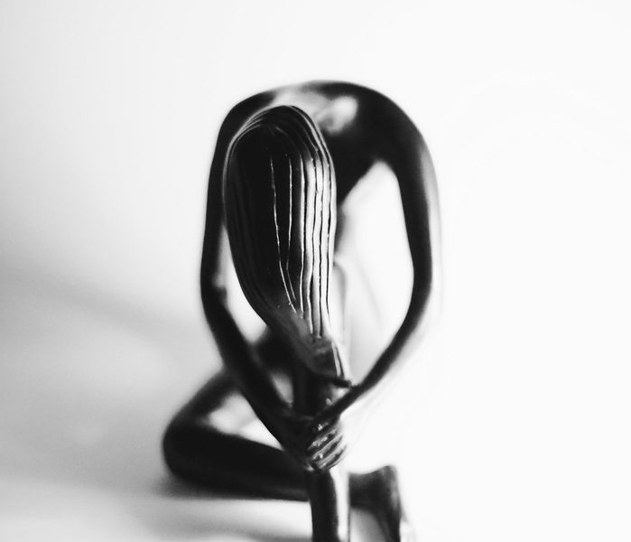 A sculpture of a woman leaning downwards