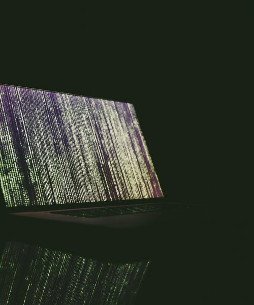An image of a laptop on a dark background. The screen wallpaper has abstract lines