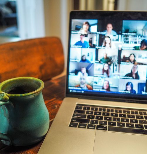 An image of a laptop and a cup held up close to it. A video conferencing platform is open on the laptop's screen, divided into squares displaying the participants' faces.