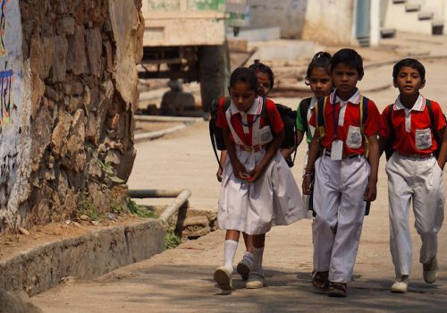 A photograph of young children walking beside a tree clad in red and white school uniform.