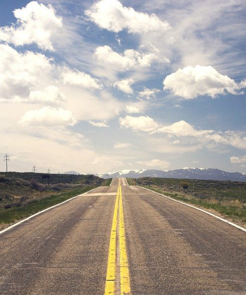 A photograph of an open, empty road in the countryside, leading to mountains.