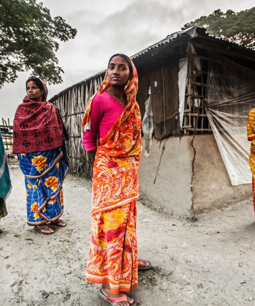 A photograph of four women, wearing sarees, standing in front of a hut. They are looking directly at the camera.