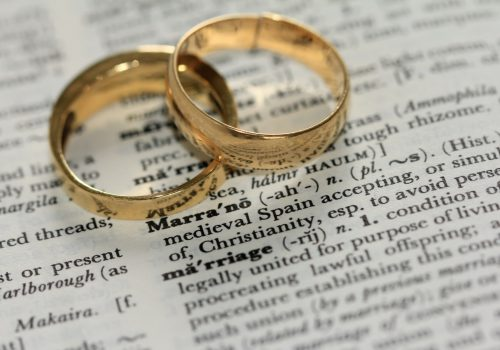 Two golden-coloured band rings atop a dictionary page zoomed in on the word 'marriage'. Above that, the definition of the word 'marrano'.