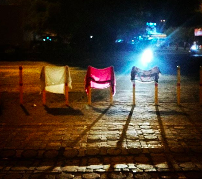 A photograph of differently coloured cloths hanging from poles in front of a train station in Mumbai, at night