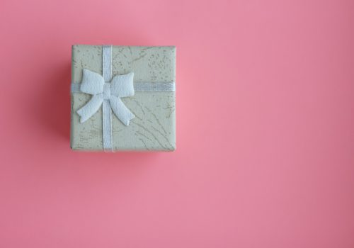 On a pink background, a blue gift-wrapped box with a bow