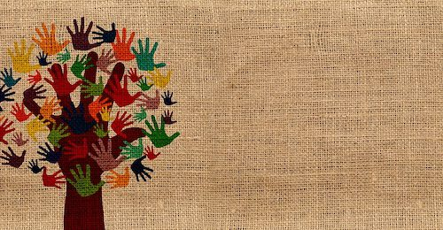 On a jute-textured background, hand-prints in different colours form the leaves of a tree, the trunk and branches of which are a hand-print.