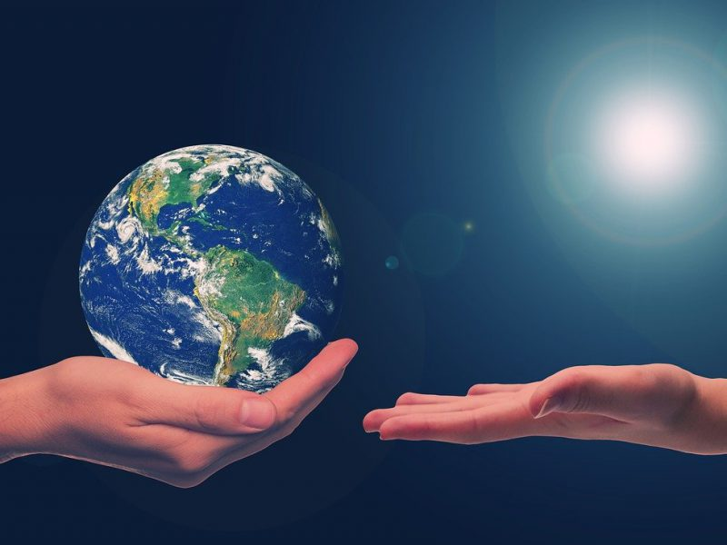 A design of two arms outstretched, one holding out the Earth in its palm and the other reaching towards it.