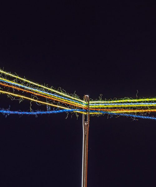 A photograph of the eye of a needle and many differently coloured threads passing through it, on a black background.