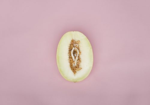 An image of a half cut pear resembling the shape of a vagina. There are seeds around it.