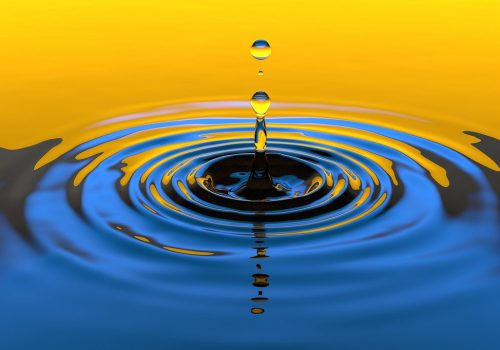 A yellow and blue gradient close-up photograph of a water droplet creating ripples