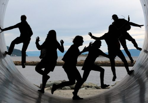 A photograph of many people's silhouettes having fun in a semi-circular course