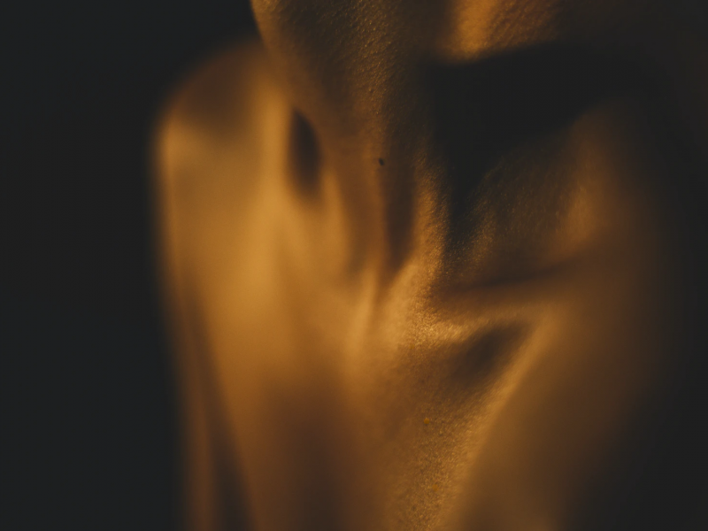 A photograph of an individual's neck and shoulders, with a focus on the collarbone.