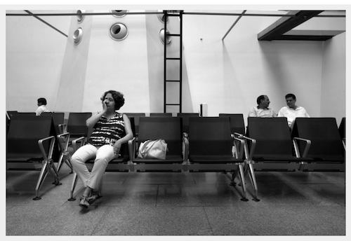 Black and white image of a woman sitting in what seems like a waiting area. Three people can be seen sitting behind her
