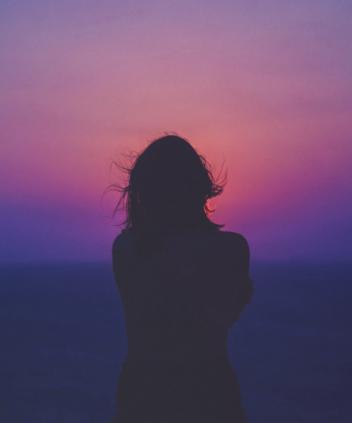 A photograph of a woman's silhouette against a pink and purple sky.