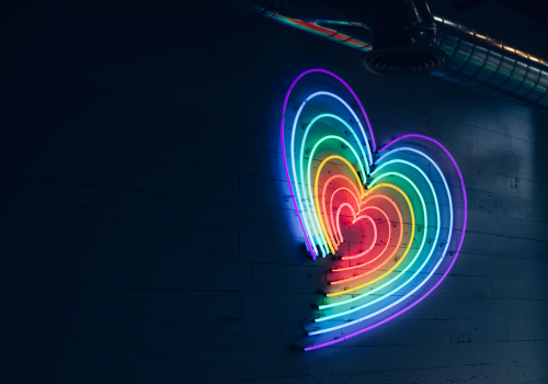 A picture of a rainbow coloured heart hanging on a wall