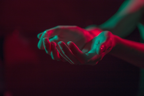 A photograph of a person's palms held out in prayer. The light is streaked with shades of pink and blue.