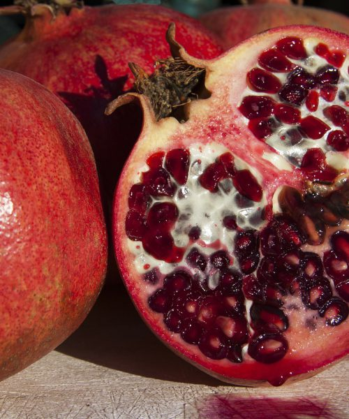 A photograph of pomegranates on a black background, one of them is cut.