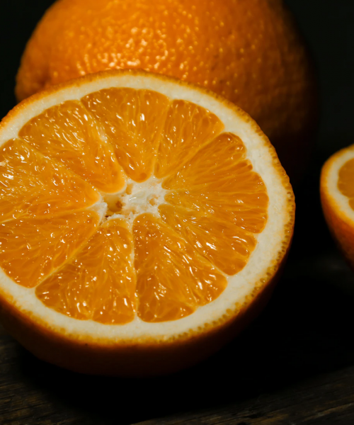 A photograph of oranges on a black background. One orange is whole and the other is halved.