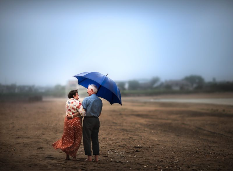 A photograph by Sujata Setia. A couple stands under a blue umbrella, holding each other, in a field.