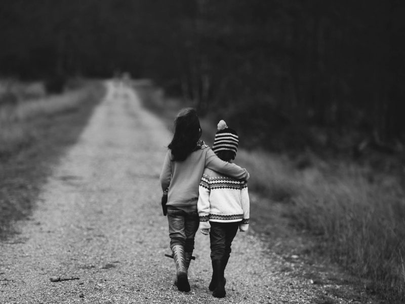 A black and white photograph of two children walking on an empty road. One child's hand is on the shoulders of the other child