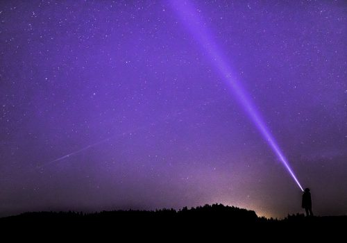 An image of a starry purple sky and a person flashing a white light towards the sky.