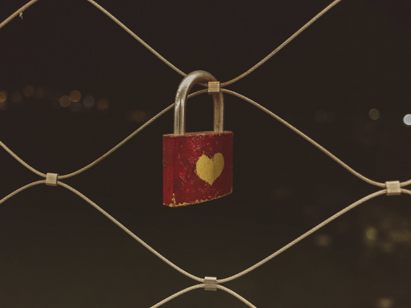 A photograph, against a dark background, of a zoomed-in fence with a square lock hanging. The lock is painted red, left un-coloured in a heart shape in the middle.