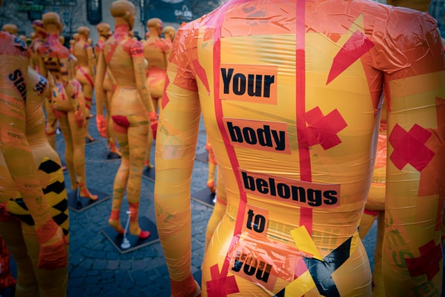 Image of mannequins with orange and pink ductapes. On one of the mannequins 'Your body belongs to you' is written