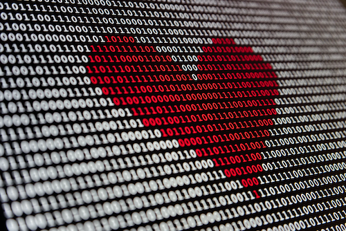 On a black background, binary digits are displayed in white, as if on a screen. In the middle is a red heart shape, made from the binary digits.