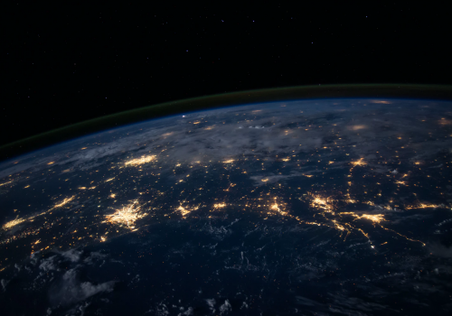 An image of a part of the Earth as seen from outer space. Only a semicircular part of the Earth has been captured, with a black background. On the surface of the Earth that is visible are golden branch-link lines and patches of golden light to indicate connectivity.