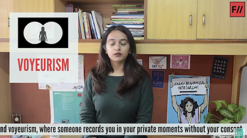 """A screenshot of Feminism in India's video How Can Women & Non-Binary People Combat Online Violence? In the middle is Japleen Pasricha, the founder of Feminism in India. She is wearing a grey-black full-sleeved shirt and her eyes are closed. She has deep brown hair reaching under her shoulders on both sides. Behind her is a wooden cupboard stacked with books, and a poster in blue with a woman holding a sign saying 'SMASH BRAHMINICAL PATRIARCHY'. On her left is an illustration that says, in pink, VOYEURISM and above it, an illustration with white circles on black to denote binoculars and a woman's silhouette at the centre. At the bottom of the screenshot are the subtitles: """"(a)nd voyeurism, where someone records you in your private moments without your consent."""""""
